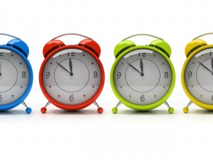 four colourful alarm clocks isolated on white background 3d