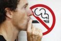 man smoking a no-smoking sign