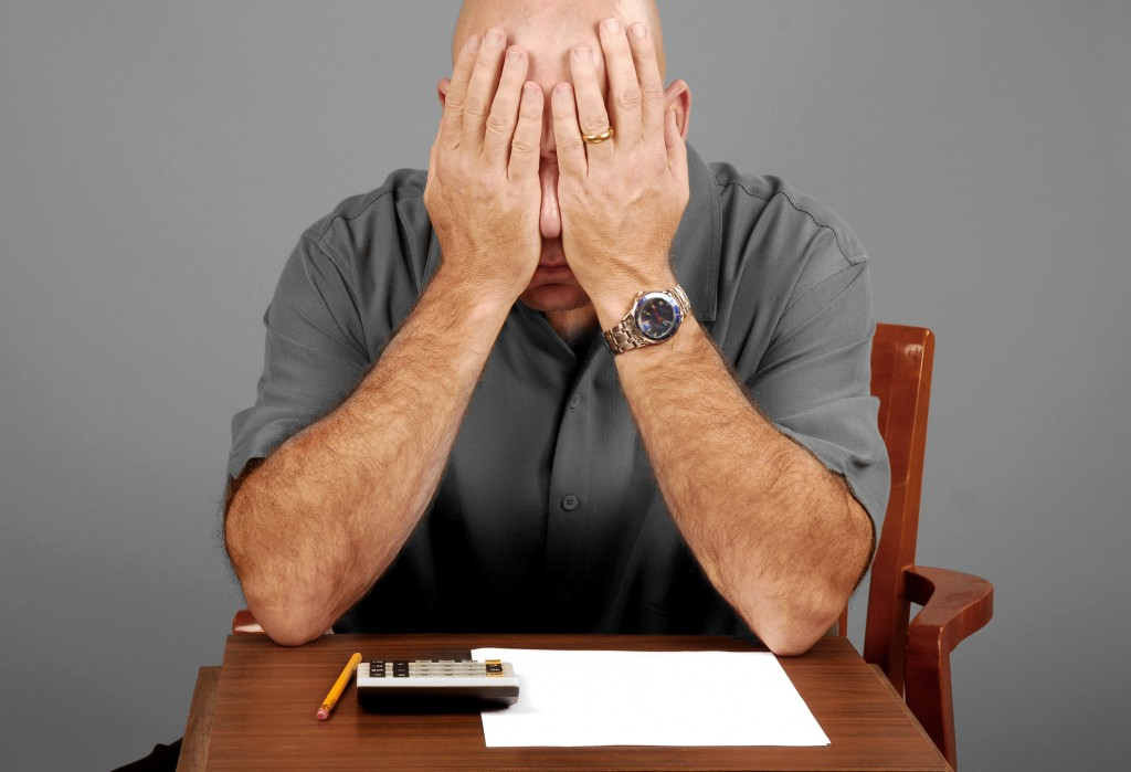 Man showing signs of stress while working budget