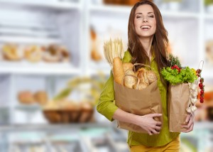 Woman with a grocery bag full of bread